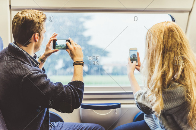Young couple taking smartphone photographs through train carriage window, Italy