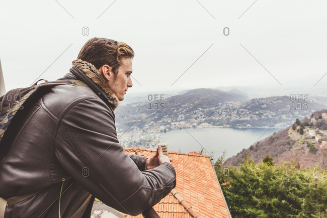 Young man looking out from roof terrace at misty Lake Como, Italy