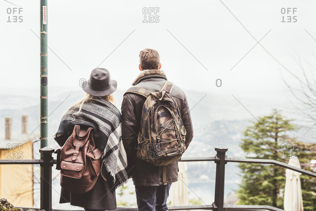 Rear view of young couple looking out at misty Lake Como, Italy