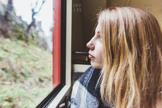 Young woman staring through funicular window, Como, Italy
