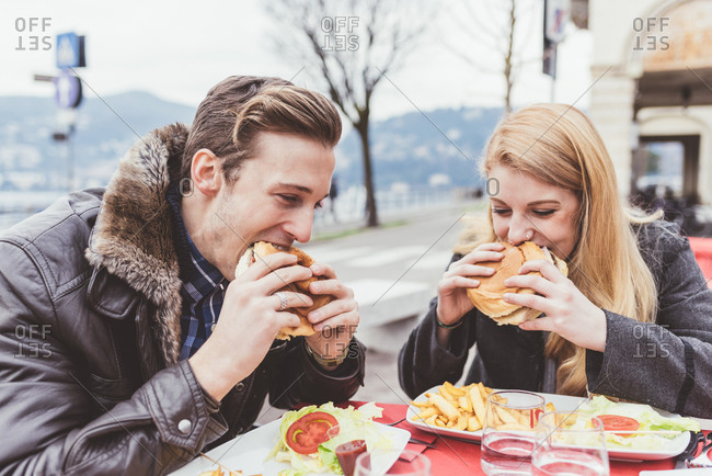 Young couple eating burgers at sidewalk cafe, Lake Como, Italy