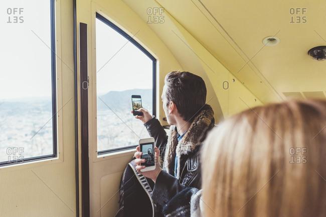 Young man taking smartphone photographs through funicular window, Como, Italy