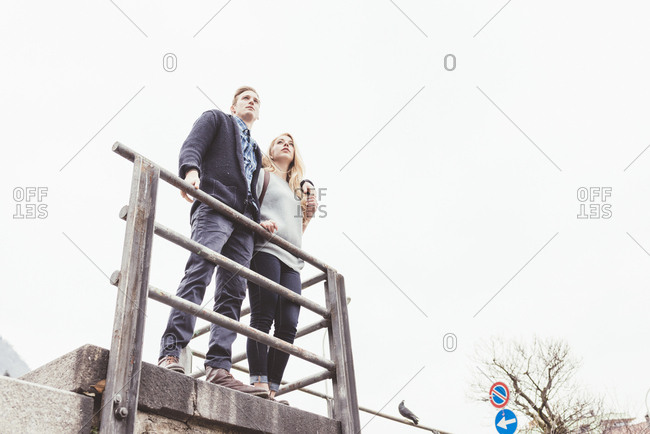 Low angle view of young couple looking out from harbor wall, Lake Como, Italy
