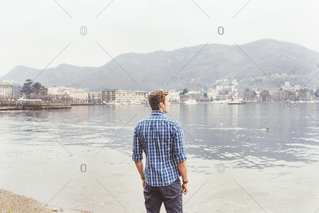 Young man looking out from lakeside, Lake Como, Italy