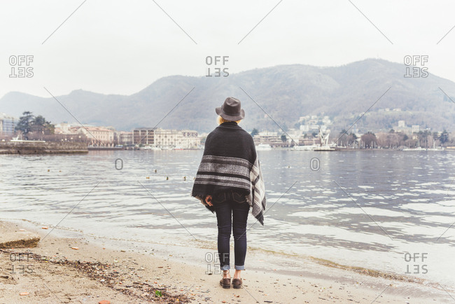 Rear view of stylish young woman looking out from lakeside, Lake Como, Italy