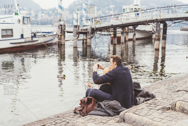 Young couple sitting photographing from lakeside, Lake Como, Italy