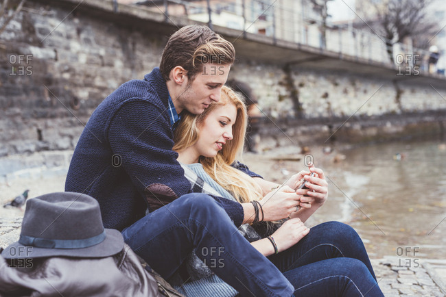 Young couple reading smartphone texts on lakeside, Lake Como, Italy