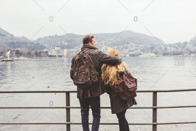 Rear view of young couple looking out on lakeside, Lake Como, Italy