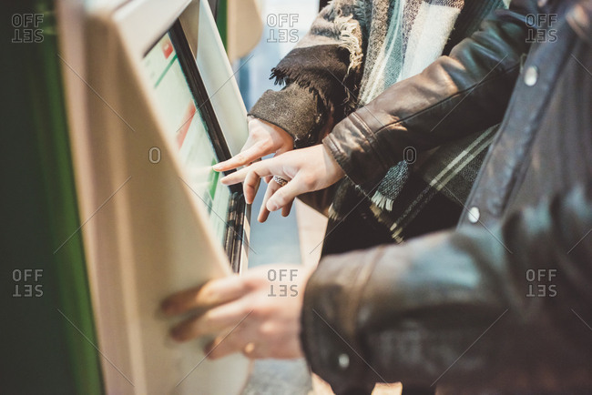 Young couple buying train tickets using touchscreen ticket machine