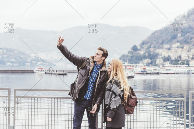 Young couple on lakeside taking smartphone selfie, Lake Como, Italy