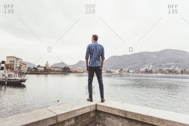 Rear view of young man standing on harbor wall looking out, Lake Como, Italy
