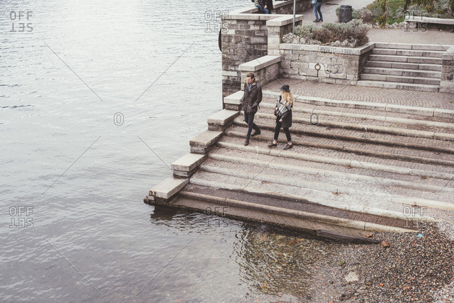 High angle view of young couple strolling down harbor stairs, Lake Como, Italy