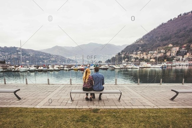 Rear view of young couple sitting on bench looking out to Lake Como, Italy