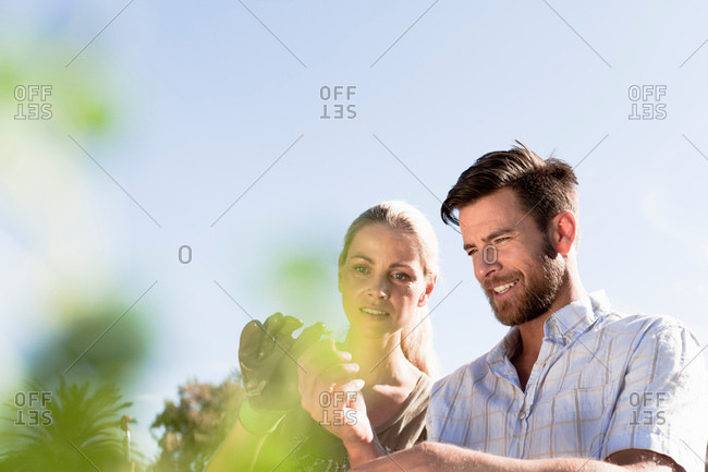 Mature couple inspecting plants in garden