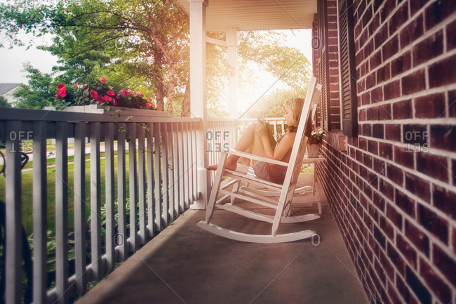 Girls on porch in rocking chair using digital tablet