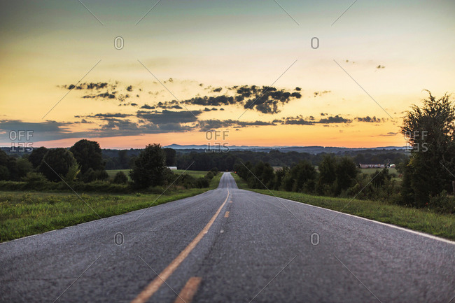 Diminishing perspective of rural road at sunset