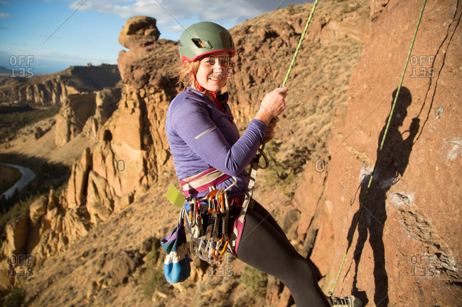 Woman rock climbing looking at camera smiling