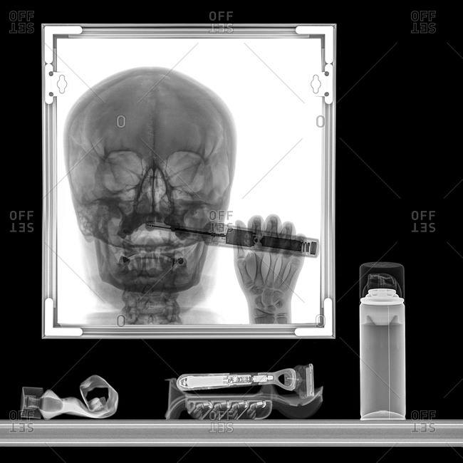 X-ray of a person brushing teeth in bathroom mirror
