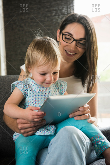 Mother teaching daughter to use digital tablet at home