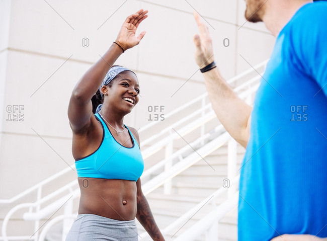 High angle view of man and woman training, high fiving on stairway at sport facility, downtown San Diego, California, USA
