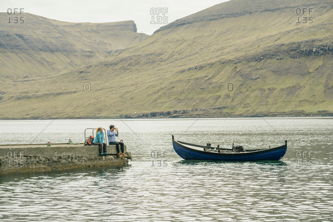 Hikers on pier, Vagar, Faroe Islands