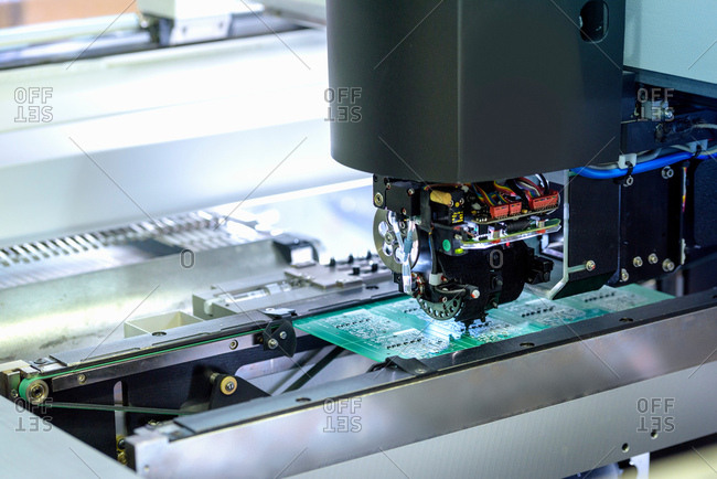 Robot placing components onto circuit board in circuit board assembly factory