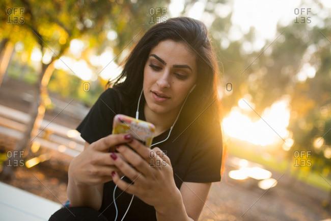 Young woman, outdoors, wearing earphones, holding smartphone
