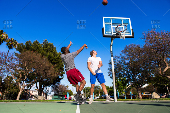 Young man throwing basketball towards basketball net on outdoor court