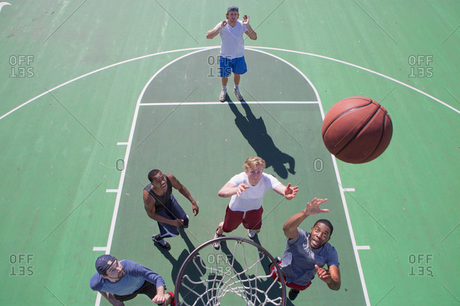 Group of male friends playing basketball on outdoor court, elevated view