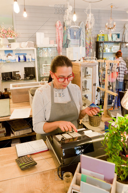 Female sales assistant using till at checkout in gift shop