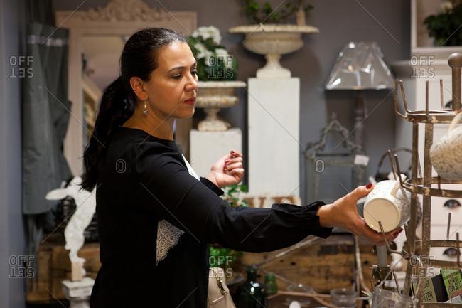 Mature female shopper browsing mugs in gift shop