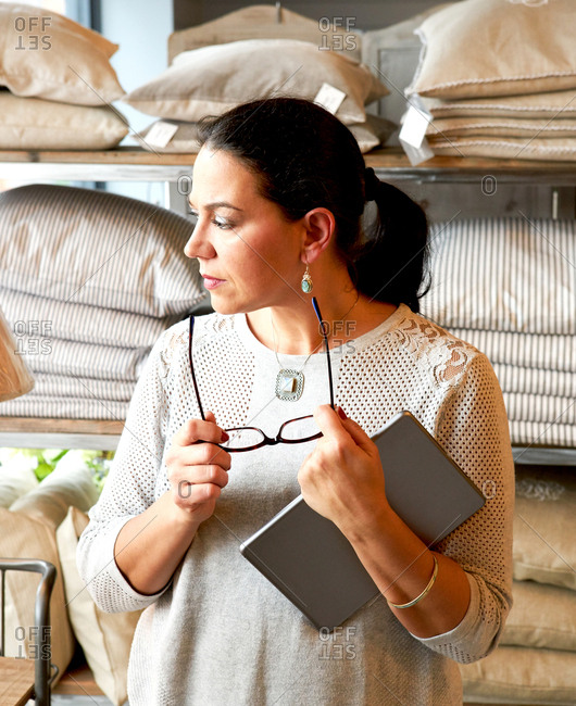 Mature female customer gazing at cushions in gift shop