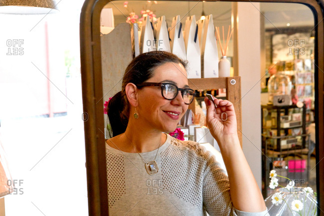 Mirror image of mature female customer trying on spectacles in gift shop