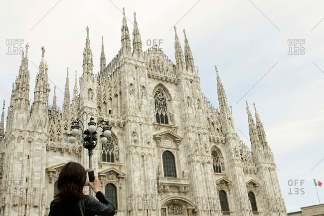 Female tourist photographing Milan Cathedral on smartphone, Milan, Italy