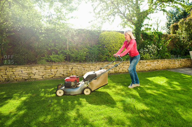 Mature woman mowing sunlit garden lawn with lawn mower