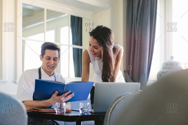 Young male chef showing menu to female manager in restaurant