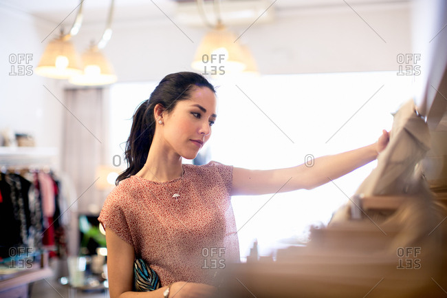 Young woman browsing clothing in boutique