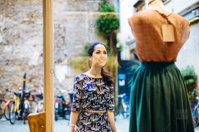Young woman looking at retro style clothing through boutique window