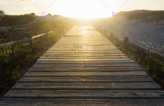 Diminishing perspective of wooden pier in sunlight, Bloubergstrand beach, Cape Town, South Africa