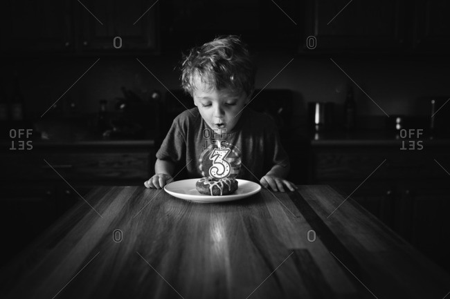 Boy blowing out candle on his cake