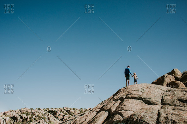 Boy and man atop rock summit