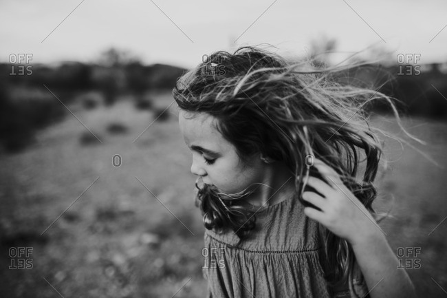 Girl holding windblown hair back