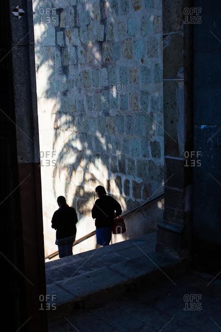 Two people walking down stairs in Oaxaca de Juarez, Mexico