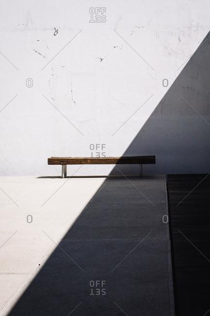 Bench along a wall hidden in shadow
