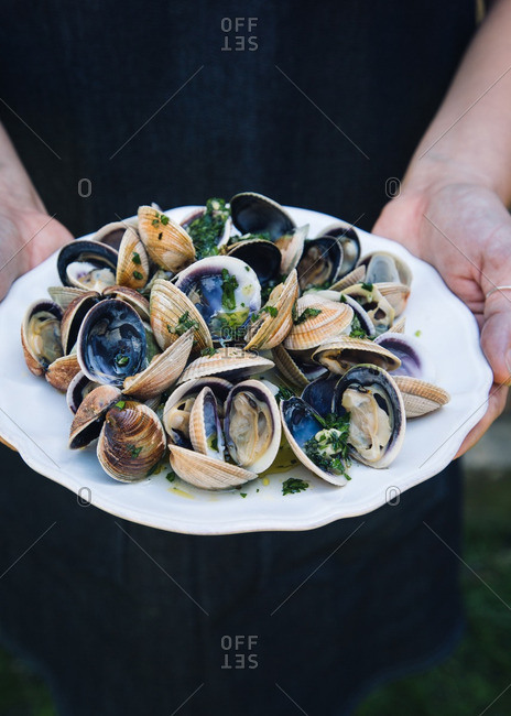 Man holding a plate of grilled clams