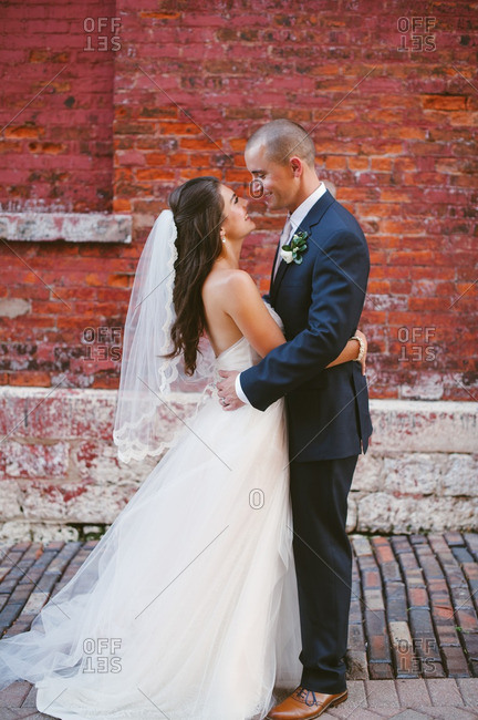 Bride and groom standing face-to-face near a brick wall