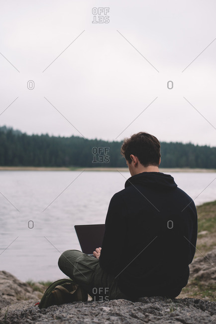 Man with a laptop by remote lake