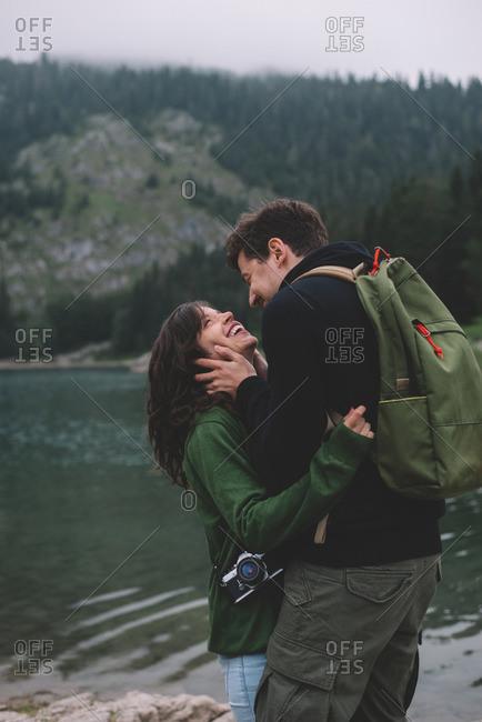 Gleeful couple by rural lake