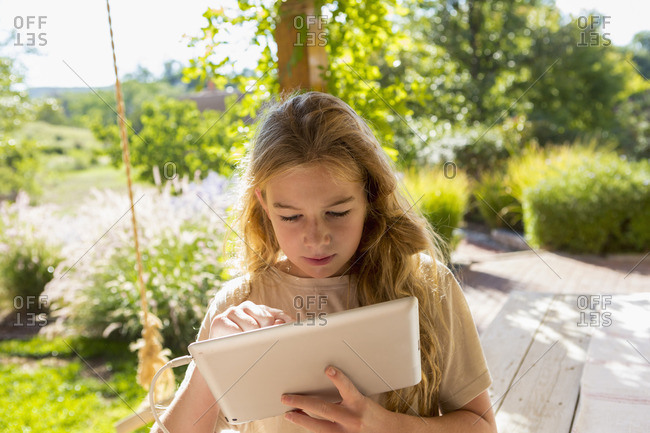 Girl in yard looking at a tablet