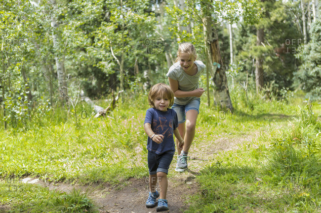 Girl chasing boy on forest trail